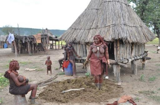 15 Himba lady tramping on cow dung to make her floor.