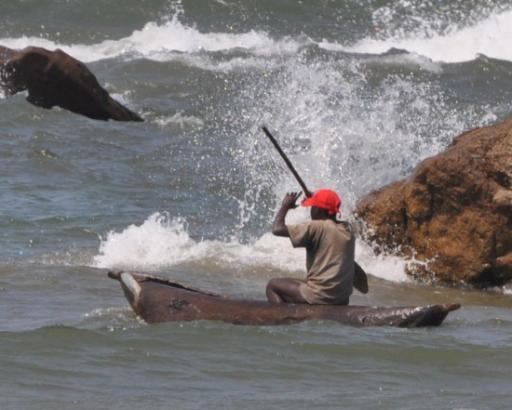 Fisherman going out in his bwota, Dedza pottery camp beach.
