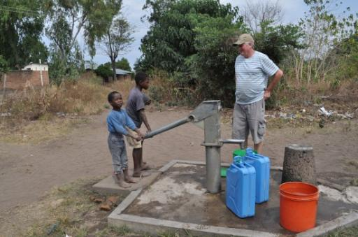 2 Children eager to fill our gerrie cans - the village water was better than Kande Beach!